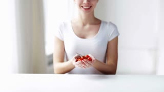 healthy eating, dieting, vegetarian food and people concept - close up of young woman showing cherry tomatoes bunch at home