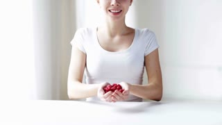healthy eating, dieting, vegetarian food and people concept - close up of young woman showing raspberries at home