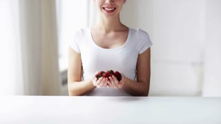 healthy eating, dieting, vegetarian food and people concept - close up of young woman showing strawberries at home