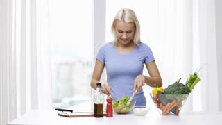 healthy eating, vegetarian food, cooking, dieting and people concept - smiling young woman dressing vegetable salad at home