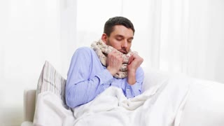 home, healthcare and medicine concept - ill man with flu at home sneezing and blowing nose