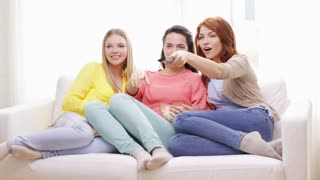 home, technology and friendship concept - three smiling teenage girls watching tv at home and eating popcorn