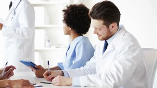 hospital, profession, medical education, people and medicine concept - group of doctors or interns with clipboards listening to mentor and writing at seminar or lecture in hospital
