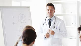 hospital, profession, medical education, people and medicine concept - group of happy doctors meeting at presentation or interns with mentor and flip board in hospital