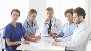 hospital, profession, people and medicine concept - group of doctors meeting on conference or medical seminar and looking to something at hospital