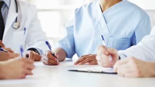 hospital, profession, people and medicine concept - group of happy doctors hands with clipboards and pens writing at meeting in hospital