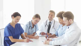 hospital, profession, people and medicine concept - group of happy doctors meeting on conference or medical seminar and looking to something at hospital