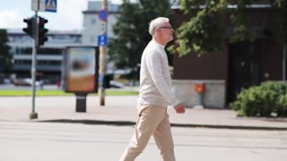 leisure and people concept - senior man walking along summer city street