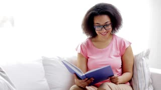leisure, literature and people concept - smiling african american young woman in eyeglasses reading book at home
