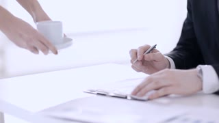 man having a coffee break while signing a contract