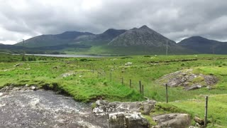 nature and landscape concept - view to river rapids and hills or mountains at connemara in ireland