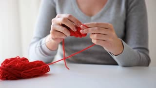 people and needlework concept - woman knitting with needles and red yarn
