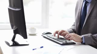 people, business, technology and office work concept - close up of businessman hands typing on computer keyboard and drinking coffee