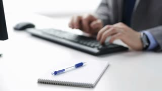 people, business, technology and office work concept - close up of businessman hands typing on computer keyboard and writing to notepad