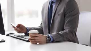 people, business, technology and office work concept - close up of businessman with smartphone drinking coffee