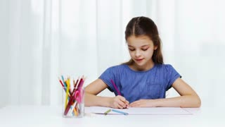 people, childhood, creativity and art concept - happy girl with colour pencils and album drawing at home