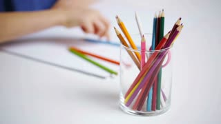 people, childhood, creativity and art supplies concept - colour pencils in glass and girl drawing on paper