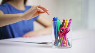 people, childhood, creativity and art supplies concept - felt-tip pens in glass and girl drawing on paper