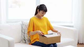 people, delivery, commerce, shipping and shopping concept - happy asian young woman taking jeans out of cardboard parcel box at home