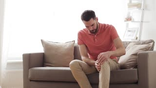people, healthcare and problem concept - unhappy man suffering from pain in leg at home