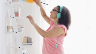 people, housework and housekeeping concept - happy african american young woman in headphones with duster cleaning at home