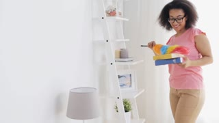 people, housework and housekeeping concept - happy woman with duster cleaning at home