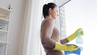 people, housework and housekeeping concept - woman in gloves cleaning window with rag and cleanser spray at home