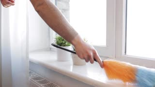 people, housework and housekeeping concept - woman with duster cleaning window sill at home