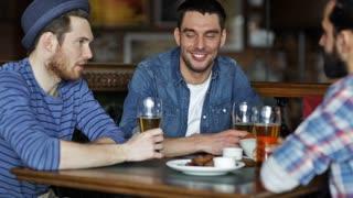 people, leisure, friendship and celebration concept - happy male friends drinking beer, eating snacks and clinking glasses at bar or pub