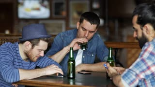 people, men, leisure, friendship and technology concept - happy male friends with smartphones drinking bottle beer at bar or pub