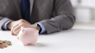 people, money saving, investing, finances concept - close up of businessman putting coins into piggy bank