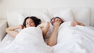 people, rest, sleeping and relationships concept - happy couple awakening in bed at home