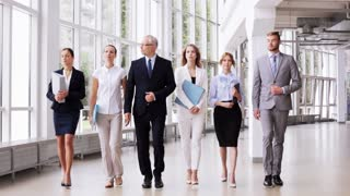 people, work and corporate concept - business team with folders walking along office building