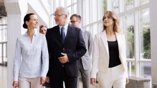 people, work and corporate concept - happy business team walking along office building and talking