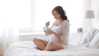 pregnancy, healthy eating, food and people concept - happy pregnant woman eating salad in bed at home
