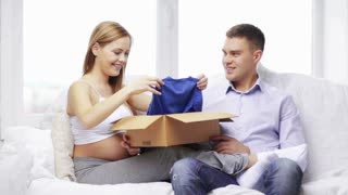 pregnancy, parenthood, happiness and delivery concept - pregnant mother and happy father looking at baby clothes