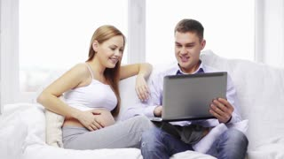 pregnancy, parenthood, happiness and technology concept - pregnant mother and happy father with laptop computer