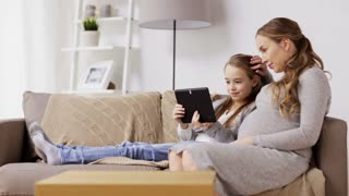 pregnancy, people, technology and family concept - happy pregnant woman and girl with tablet pc computer sitting on sofa at home