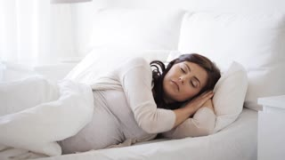 pregnancy, rest, people, comfort and sleeping concept - pregnant woman adjusting pillow in bed at home