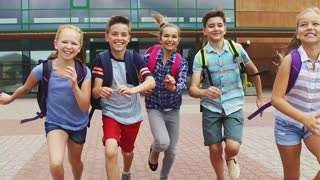 primary education, communication and people concept - group of happy elementary school students with backpacks running outdoors in slow motion mode