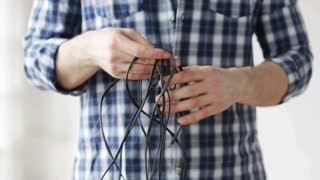 repair, building, construction and people concept - close up of man untangling wires