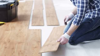 repair, building, floor and people concept - close up of man installing wood flooring