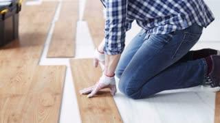 repair, building, floor and people concept - close up of man installing wood flooring