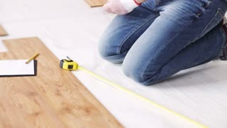 repair, building, floor and people concept - close up of man measuring flooring with ruler and writing to clipboard