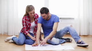 repair, building, renovation and home concept - smiling couple discussin blueprint at home