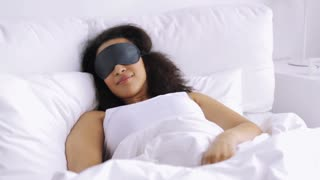 rest, comfort and people concept - young african woman in sleeping mask waking up in bed at home bedroom