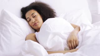 rest, sleeping, comfort and people concept - young african woman waking up in bed at home bedroom