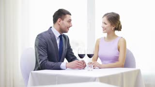 restaurant, couple and holiday concept - smiling young couple with glasses of red wine, talking and drinking wine at restaurant