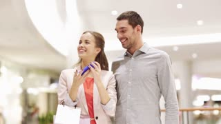 sale, consumerism, technology and people concept - happy young couple with shopping bags and smartphone taking selfie in mall