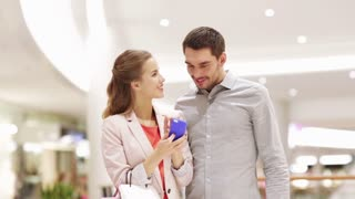 sale, consumerism, technology and people concept - happy young couple with shopping bags showing smartphone and taking selfie in mall